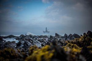 Naturskjønt bilde av kyst, med oljeplattform i bakgrunnen