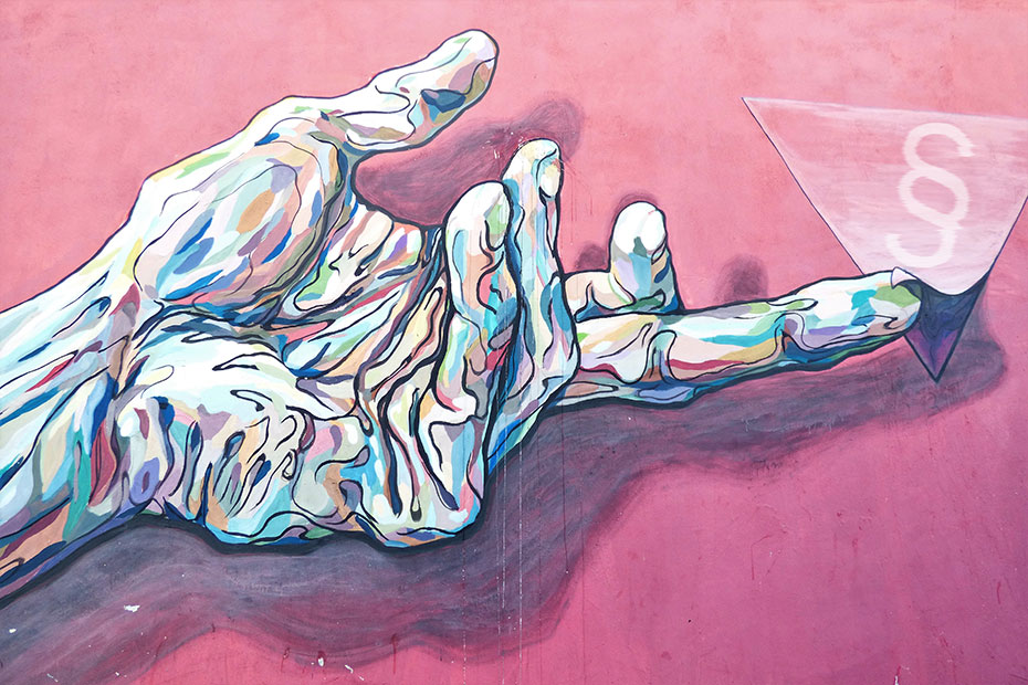 Veggmaleri med stilisert håndt som holder papirlapp med paragraftegn