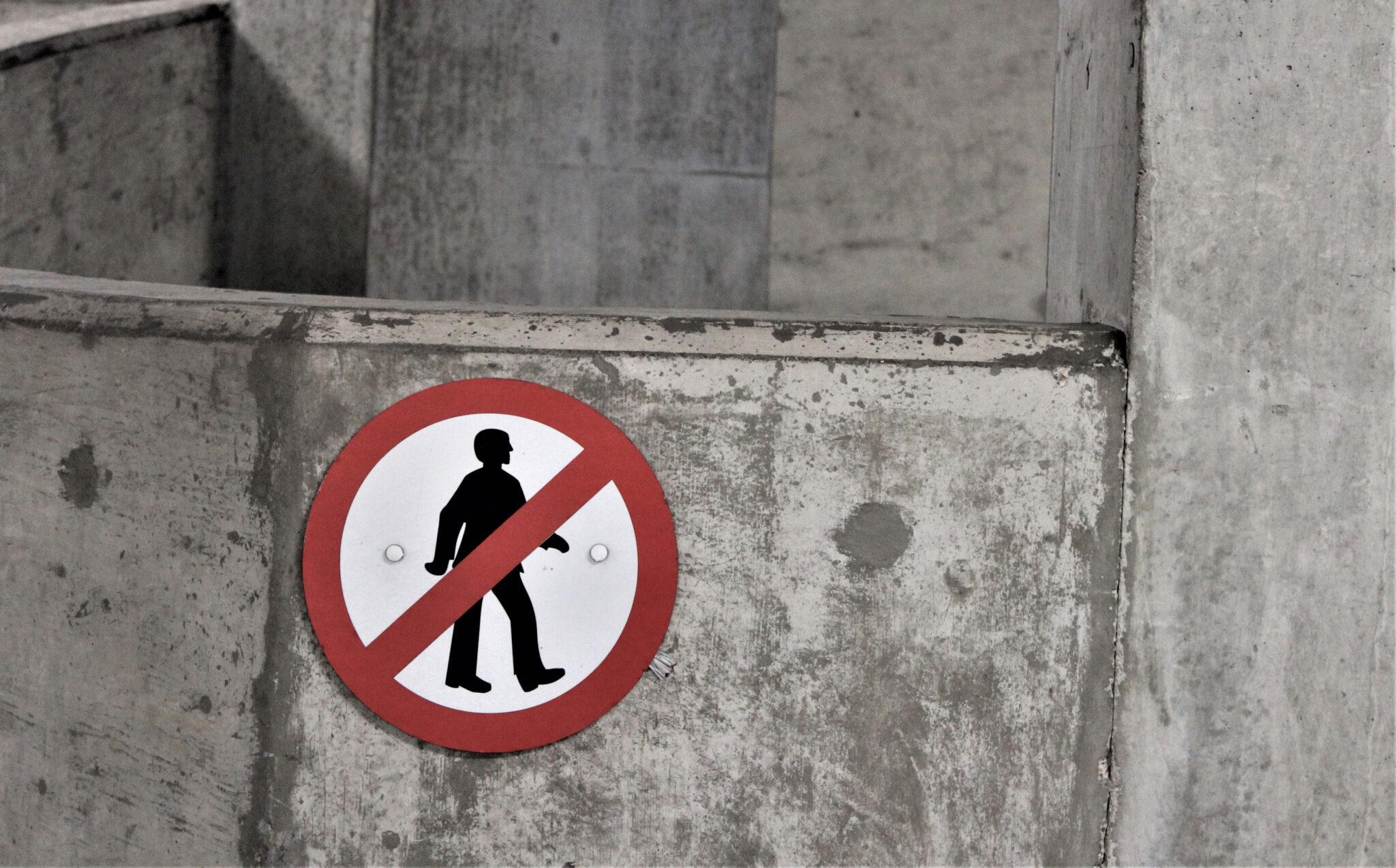 """""""Fotgjengere forbudt""""-skilt på betongvegg."""