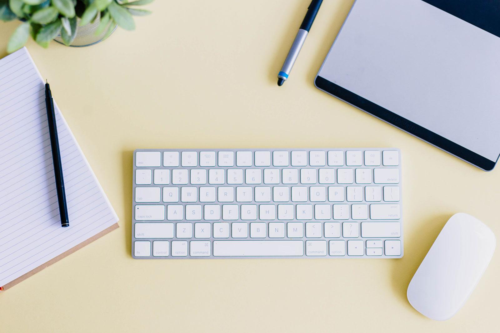 Bilde av arbeidspult med penn, papir, en grønn plante, tastatur, mus og datamaskin