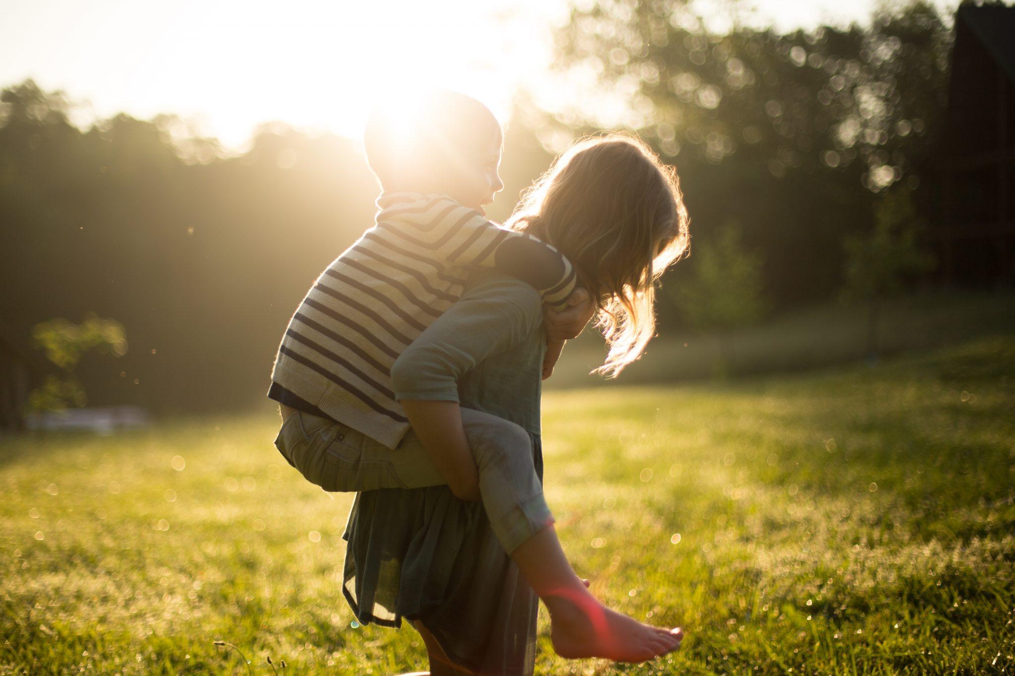 Barn som bærer et mindre banr på ryggen på en grønn plen i solnedgang