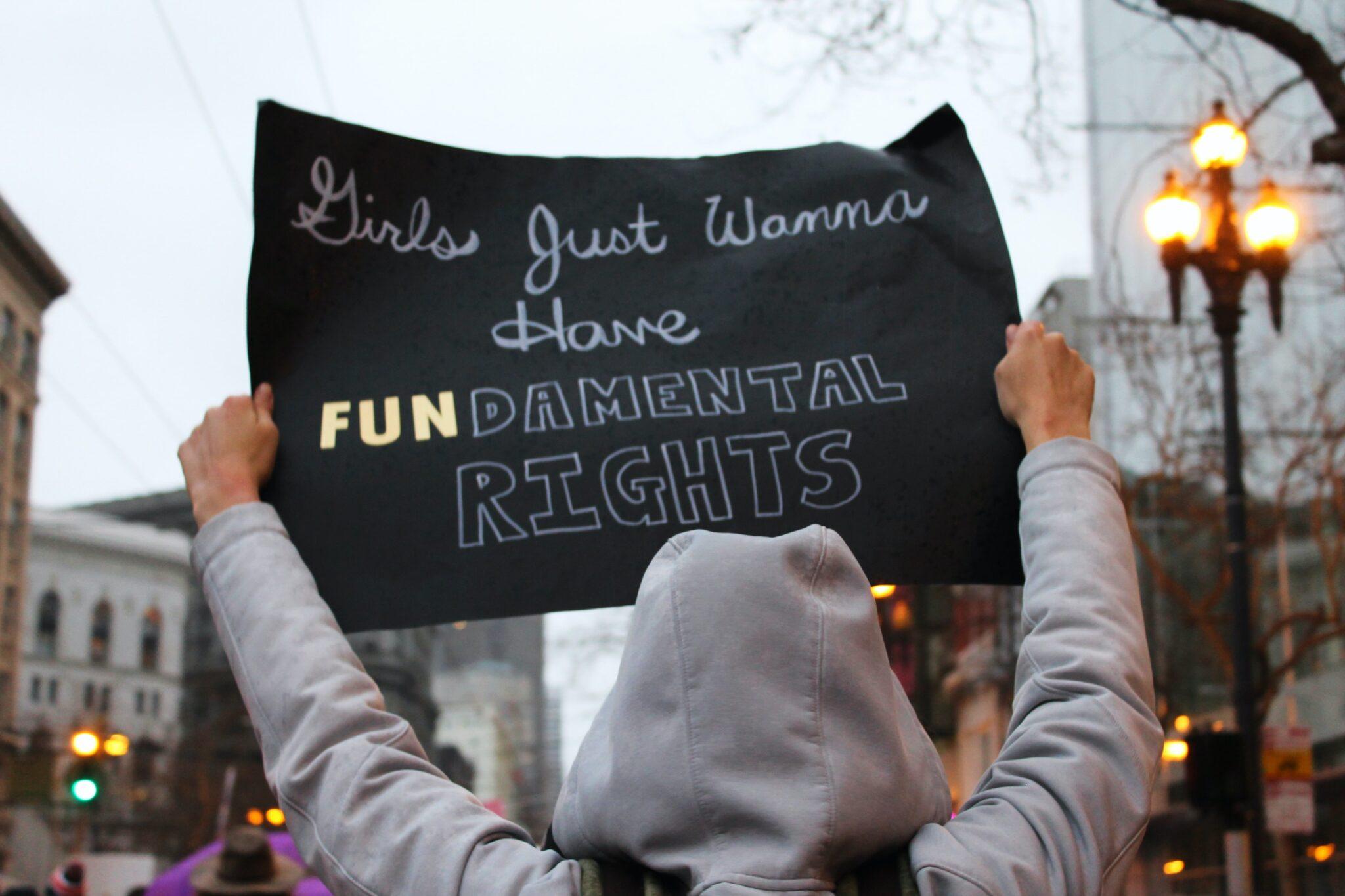 "Demonstrant i grå hettejakke som holder opp en svart plakat med skriften ""Girls just Wanna Have FUNDAMENTAL RIGHTS"""