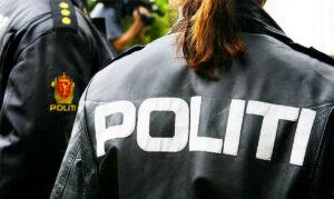 """Rygg av kvinnelig politibetjent med skriften """"POLITI"""" i store bokstaver."""