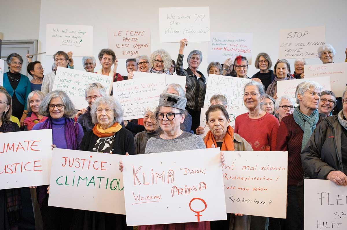 En samling eldre kvinner som holder plakater med apeller om klimatiltak