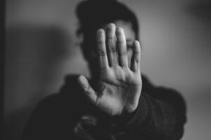 Sort-hvitt bilde av en hånd som holdes med håndflate mot kameraet, foran et ansikt